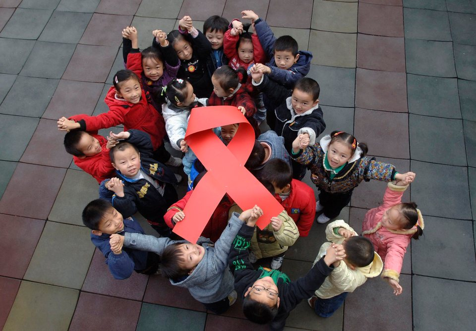 Children pose to raise a red ribbon symbol during an AIDS awareness activity at a kindergarten in Hefei